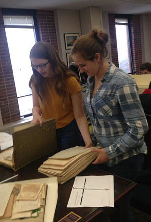Two students from Easthampton High School, looking at archival documents